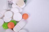 Pillen van verschillende kleuren op geld achtergrond. — Stockfoto