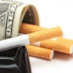 Cigarettes and money. expensive habit. white background - horizontal photo. — Stock Photo #65823331