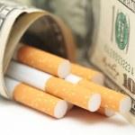 Cigarettes and money. expensive habit. white background - horizontal photo. — Stock Photo #65823333