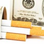 Cigarettes and money. expensive habit. white background - horizontal photo. — Stock Photo #65823429