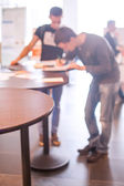 Two persons writing on table, blurred — Stock Photo