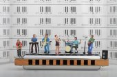 Miniature of a rock band performing on a big harmonica — Stock Photo