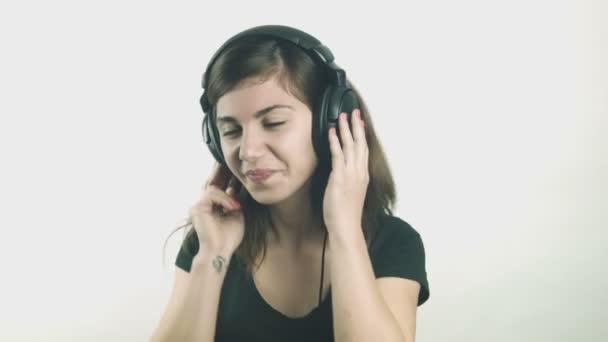 Atractiva mujer joven escuchando música con auriculares — Vídeo de stock
