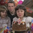 Young beautiful girl blowing candles on a birthday cake with her father and twin sister, slow motion — Stock Video #68447053
