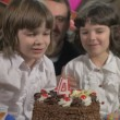 Young beautiful girl blowing candles on a birthday cake with her father and twin sister, slow motion — Stock Video #68447183