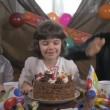 Young beautiful girl blowing candles on a birthday cake with her father and twin sister, slow motion — Stock Video #68447209
