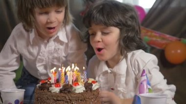 Young beautiful twin sisters blowing candles on a birthday cake, slow motion — Stock Video