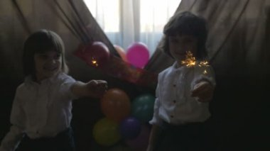 Young beautiful twin sisters playing with fireworks at a birthday party, slow motion — Stock Video