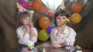 Young beautiful twin girls blowing party horns — Stock Video