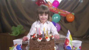 Young beautiful girl blowing candles on a birthday cake — Stock Video