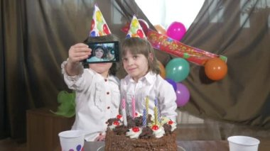 Young beautiful twin girls taking a selfie (self portrait) with a smartphone at a birthday party — Stock Video