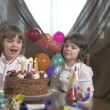 Young beautiful girl blowing candles on a birthday cake with her twin sister — Stock Video #68450037