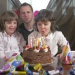 Young beautiful girl blowing candles on a birthday cake with her father and twin sister — Stock Video #68450183