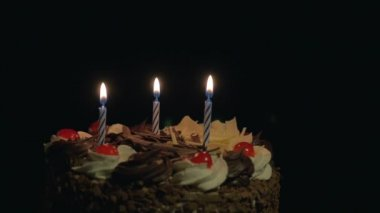 Blowing out birthday candles on delicious chocolate cake — Stock Video