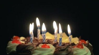 Blowing out birthday candles on a spinning delicious chocolate cake — Stock Video