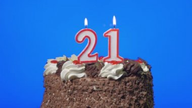 Blowing out number twenty-one birthday candles on a delicious chocolate cake, blue screen — Stock Video