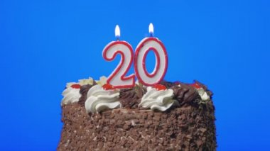 Blowing out number twenty birthday candles on a delicious chocolate cake, blue screen — Stock Video