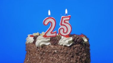 Blowing out number twenty-five birthday candles on a delicious chocolate cake, blue screen — Stock Video