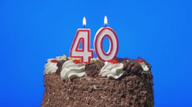 Blowing out number forty birthday candles on a delicious chocolate cake, blue screen — Stock Video