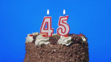 Blowing out number forty-five birthday candles on a delicious chocolate cake, blue screen — Stock Video