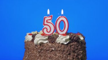 Blowing out number fifty birthday candles on a delicious chocolate cake, blue screen — Stock Video