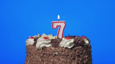 Blowing out number seven birthday candle on a delicious chocolate cake, blue screen — Stock Video