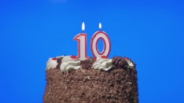 Blowing out number ten birthday candles on a delicious chocolate cake, blue screen — Stock Video