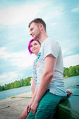 Man and woman sitting on an upturned boat — Stock Photo