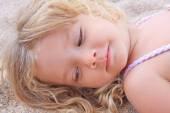 Little girl lying on the sand — Stock Photo