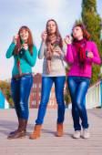 Three young beautiful women blow bubbles — Stock Photo