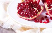Closeup sliced pomegranate on white plate — ストック写真