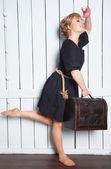 Vacker kvinna med en resväska i handen — Stockfoto