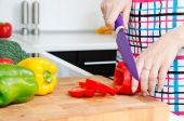 Woman chef cutting peppers. Food preparation in modern kitchen — Stock Photo