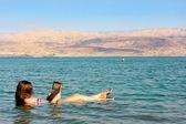 Jonge vrouw leest een boek drijvend in de dode zee in israël — Stockfoto