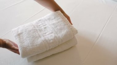 Female putting two white towels — Stok video