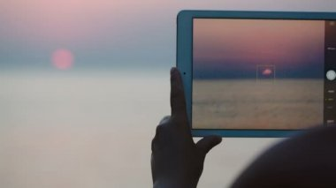 Taking pictures of sunset over sea with touch pad — Stock Video