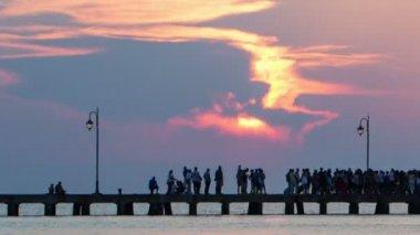 People walking on pier at sunset — Stock Video