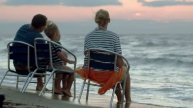 Family of three sitting on chairs by sea at sunset — Vídeo de Stock
