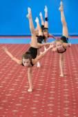молодые гимнасты женского пола, делающие вертикальный шпагат — Стоковое фото