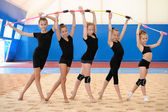 Young female gymnasts making bow with Indian clubs — Stock Photo