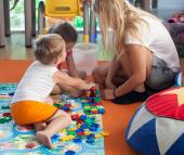 Doing puzzle with tutor in nursery — Stock Photo