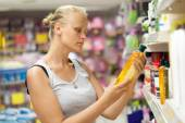 Woman looking at shampoo bottle in the store — Stock Photo