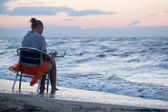Woman sitting on chair by sea and using pad — Stockfoto