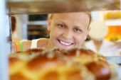 Happy woman looking at fresh bread in the shop — Stock Photo