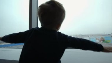 Little boy showing plane with hands looking at it out the window — 图库视频影像