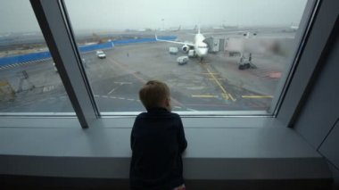 Little boy looking out the window at airport — Stock Video