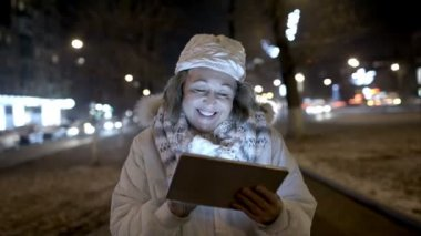 Happy woman walking in the evening street with pad — Stockvideo