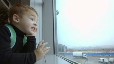 Mother and son at airport spending time looking out the window — Stock Video