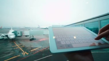 Using tablet computer by the window at airport — Stock Video