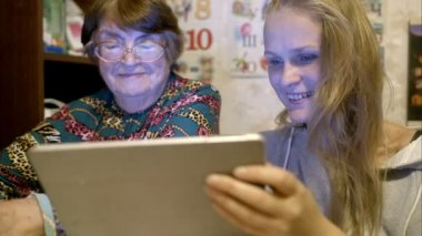 Young and senior woman looking through photos on pad — Stockvideo